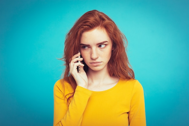 Lifestyle concept - portrait of ginger red hair girl with shocking and stressful expression while talking with friend by mobile phone. isolated on blue pastel background. copy space.