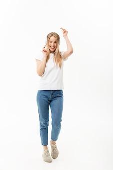 Концепция образа жизни: портрет веселой счастливой студентки, слушающей музыку в наушниках во время танцев, изолированные на белом фоне