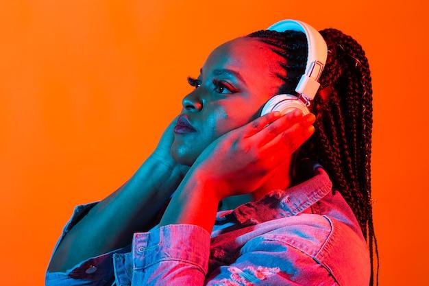 라이프 스타일 개념-음악을 듣고 즐거운 아름다운 아프리카 계 미국인 여자의 초상화.