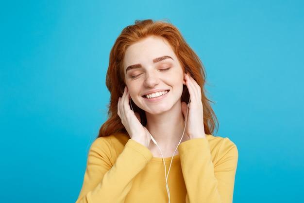 Портрет концепции образа жизни веселая счастливая рыжая девушка с красными волосами наслаждается прослушиванием музыки в наушниках, радостной улыбкой, изолированной на синей пастельной стене копией пространства