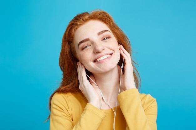 ライフスタイルの概念 - 明るい幸せなジンジャー赤毛の女の子の肖像画は、楽しい笑顔のカメラにヘッドホンで音楽を聞くことをお楽しみください。青いパステルの背景に隔離されています。スペースをコピーします。
