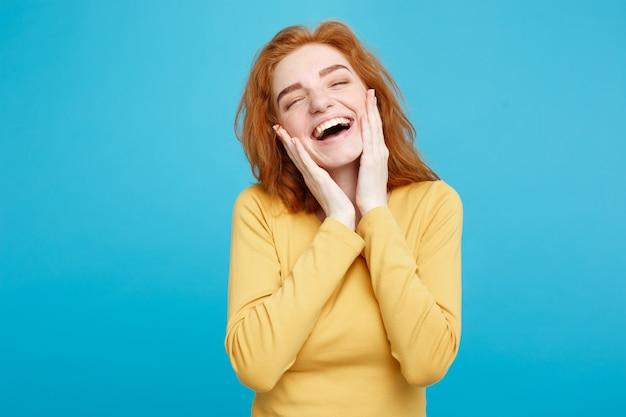Портрет концепции образа жизни веселой счастливой рыжей девушки с рыжими волосами с радостной и захватывающей улыбкой, изолированной на синей пастельной стене копией пространства