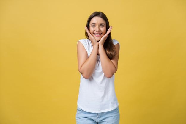 ライフスタイルの概念-カメラを見ているあごに手で笑っている若いスタイリッシュな女の子の肖像画。イエローゴールドの背景。スペースをコピーします。