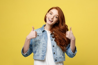 Lifestyle Concept: Satisfied successful girl with thumb up gesture on golden yellow background
