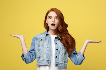 Lifestyle Concept: Surprised young woman with hand on side over golden yellow background