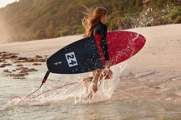 Concetto di stile di vita. la vista del surfista veloce corre sulla spiaggia, fa schizzi dall'acqua, ha fretta