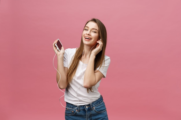 Lifestyle concept. young woman using phone for listening to music on pink background