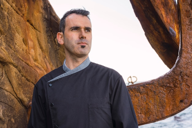 Lifestyle of a cook, caucasian cook with black apron in a photo on the coast