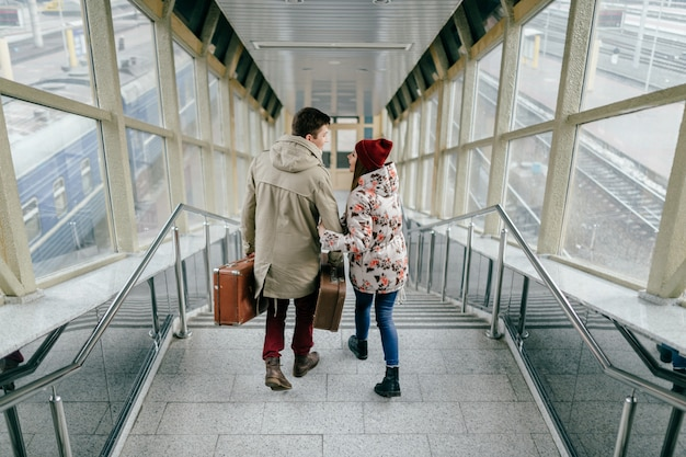 Lifestyle couple of young happy lovers carry vintage brown suitcases at railway station. pair of stylish cheerful hipsters going down the stairs.