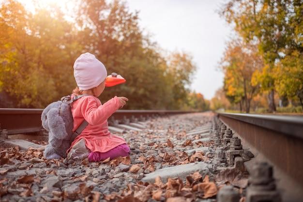 생활 양식. 귀여운 소녀는 버려진 철도 트랙에서 야외에서 놀고 있습니다.