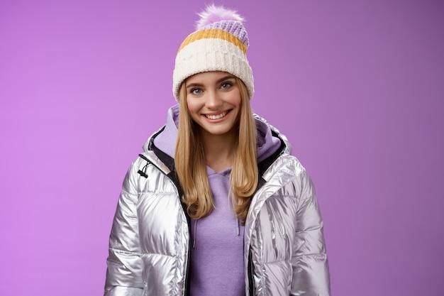 생활 양식. 따뜻하고 아늑한 재킷 모자 스키 리조트 휴가를 입고 귀여운 젊은 금발 유럽 여자 재미 웃는 임대 장비를 웃 고 행복 하 게 보라색 배경 서 스노우 보드를 배우고 싶어.