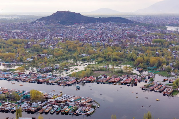 Lifestyle in dal lake, man drive the boat in middle of the dal lake and mountain backgrou