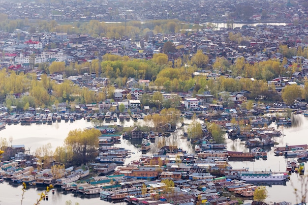 Lifestyle in dal lake, man drive the boat in middle of the dal lake and mountain backgroun