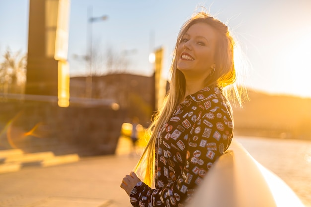 Lifestyle, detail of a portrait of a young blonde in the city of bilbao at a sunset