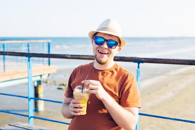 라이프 스타일, 음료 및 사람들 개념. 일회용 커피 프라페를 마시는 선글라스 남자