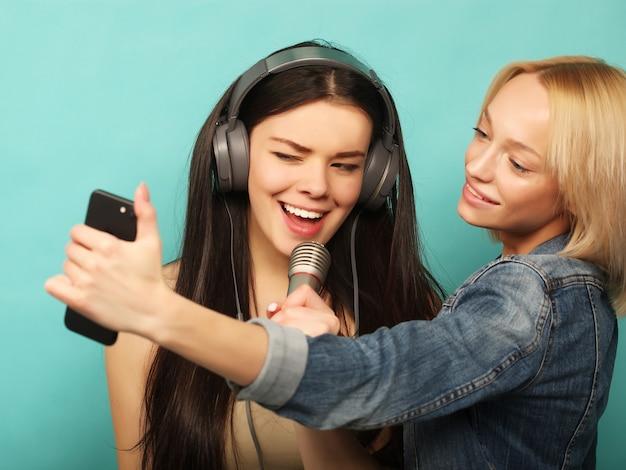ライフスタイル、感情、人々のコンセプト。マイクと幸せな若い女の子は青のスマートフォンで写真を撮る