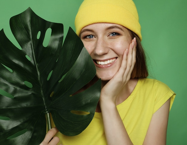 Lifestyle, emotion and people concept: smiling beautiful woman behind big leaf
