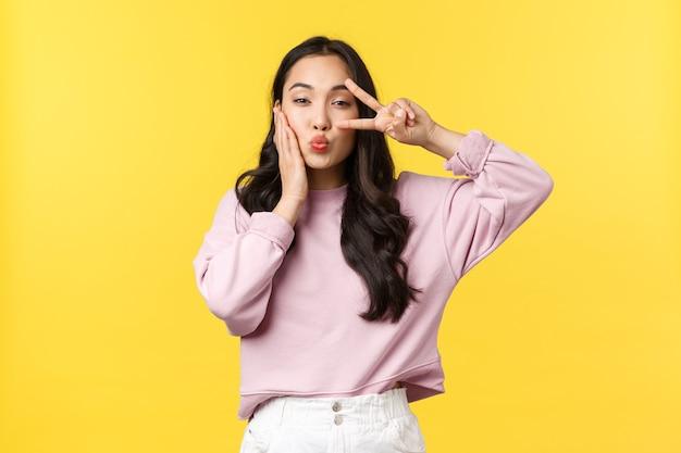Образ жизни, эмоции и концепция рекламы. кокетливая и милая, стильная азиатская женщина показывает знак мира каваий поверх глаз и складывает губы для поцелуя, чувствуя себя красивым, желтый фон.