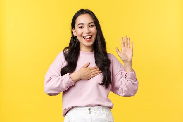 라이프 스타일, 감정 및 광고 개념입니다. 정직하고 진심으로 행복한 미소 짓는 아시아 여성은 진실을 말하고, 마음에 맹세하고 한 손을 들고 노란색 배경에 서 있다고 약속합니다.