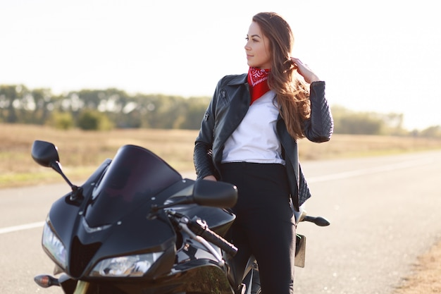 Lifestyle, extreme and people concept. sideways shot of pretty thoughtful young female driver dressed in fashionable clothes, stands near favourite motorbike, poses outdoor, enjoys fast driving