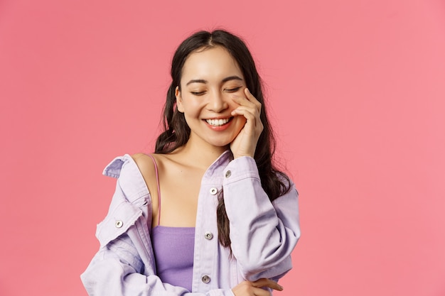 Lifestyle, fashion and beauty concept. close-up portrait of cheerful, lovely young asian woman close eyes, enjoying day, laughing happily, touch clean skin, pink wall