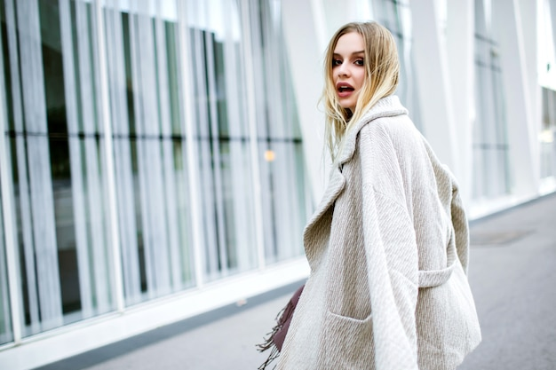 流行のスタイリッシュな服、バイオレットの長いスカーフ、カシミヤの高級コート、ミディドレスを着てかなりエレガントな女性のライフスタイルファッションポートレート、笑顔を楽しんで、モダンなビジネスセンターの前に滞在