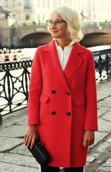 かわいい流行の服を着て、通りを歩いている若いスタイリッシュな女性のライフスタイルファッションの肖像画
