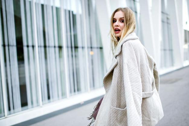 Ritratto di moda stile di vita di donna abbastanza elegante che indossa abiti alla moda alla moda, sciarpa lunga viola, cappotto di lusso in cashmere e abito midi, sorridere alla fine godendo, stare di fronte al moderno centro business