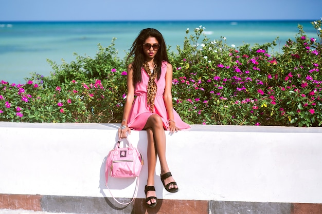 Lifestyle fashion portrait of pretty young thai asian woman posing near beach at luxury hotel and enjoy her vacation, trendy pink dress, leopard scarf and sunglasses, travel mood.
