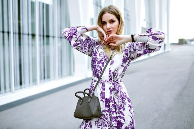 Ritratto di modo di stile di vita della donna bionda graziosa alla moda in posa sulla strada vicino al moderno centro business, indossando la borsa e gli accessori del vestito floreale glamour, colori tenui.