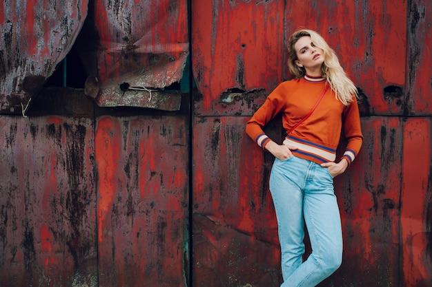 Lifestyle fashion portrait of young beautiful cute girl model.  odd  strange unusual cute naughty blonde woman posing on old rusty metal gate
