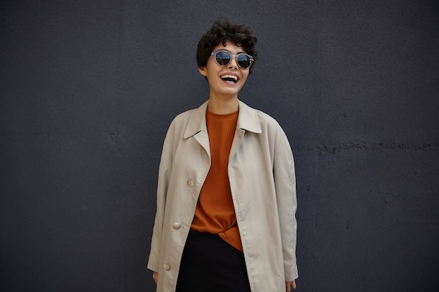 Lifestyle fashion portrait of young stylish hipster woman with short haircut wearing sunglasses, posing outdoor during lunch break, being in high spirit and laughing happily