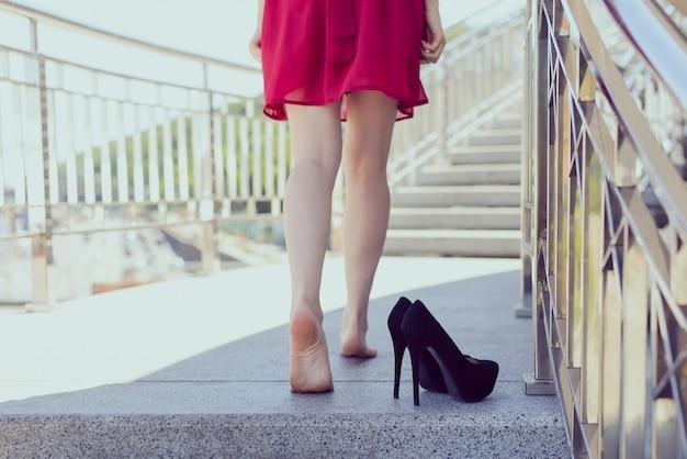 仕事帰りのアーバンスタイルのコンセプトで疲れ果てたライフスタイルフリーダムパーティー。後ろ後ろローアングルクローズアップセクシーフィットスリムで美しいスポーティな愛の脚のステップを踏む写真、黒いハイヒールパンプス