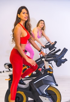 Lifestyle of friends training in a gym. bicycle training a caucasian girl and a latin girl