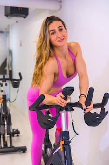 Lifestyle of friends training in a gym,. bicycle training a caucasian girl in pink