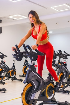 Lifestyle of friends training in a gym,. bicycle training a hispanic girl