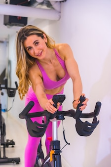 Lifestyle of friends training in a gym,. caucasian girl training on a bicycle