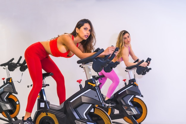 Lifestyle of friends training in a gym,. cycling a caucasian girl and a latin girl