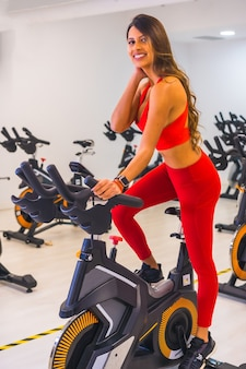 Lifestyle of friends training in a gym,. portrait of a girl training a hispanic girl on a bicycle