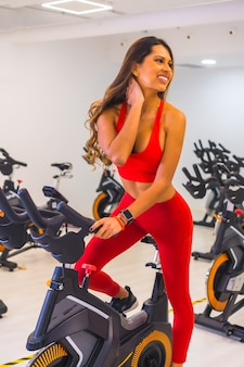 Lifestyle of friends training in a gym,. portrait of a pretty girl training a hispanic girl on a bicycle