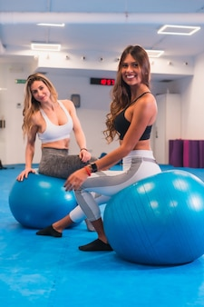 Lifestyle of friends training in a gym,. portraits of a latin girl and a caucasian blonde in a ball