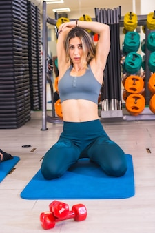 Lifestyle of friends training in a gym, sports and wellness in salur. caucasian girl doing stretching on a mat