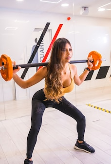 Lifestyle of friends training in a gym, sports and wellness in salur. girl training doing squats with dumbbells