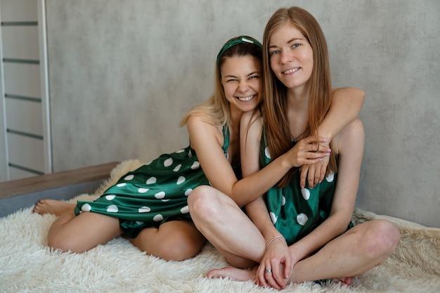 Концепция образа жизни, дружбы и людей - две красивые девушки, одетые в пижаму, обнимаются и улыбаются