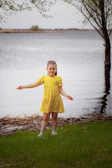 Lifestyle fulllength portrait of a girl in a yellow dress on the riverbank enjoying a warm spring da...