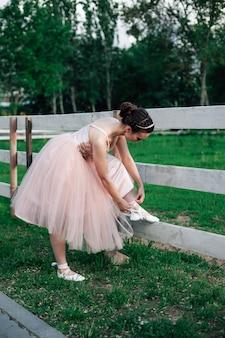 フルオーガンザのスカートが付いたピンクのドレスを着たバレリーナのライフスタイルのフルレングスの肖像画は、下に曲がります...