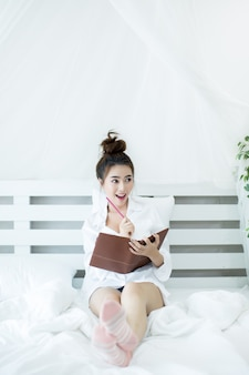 Lifestyle happy young asian woman enjoying lying on the bed reading book at home.
