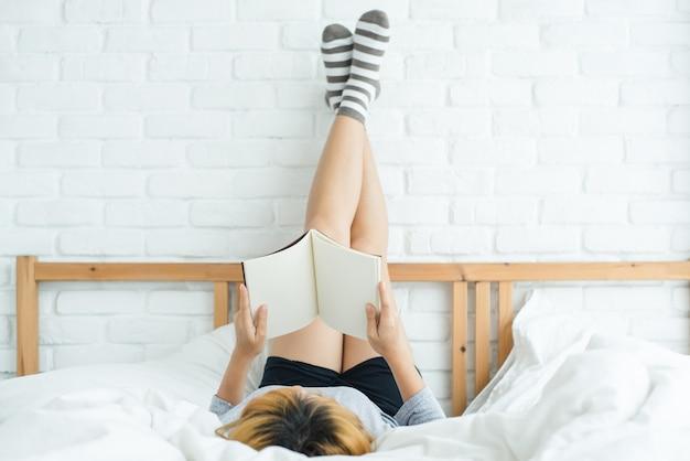 Giovane donna asiatica felice di stile di vita che gode della menzogne sul piacere del libro di lettura del letto in abbigliamento casuale