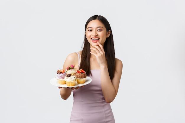 라이프 스타일, 휴일, 축하 및 음식 개념. 이브닝 드레스 파티의 아름 다운 젊은 아시아 여자 호스트, 맛있는 디저트로 손님을 대우