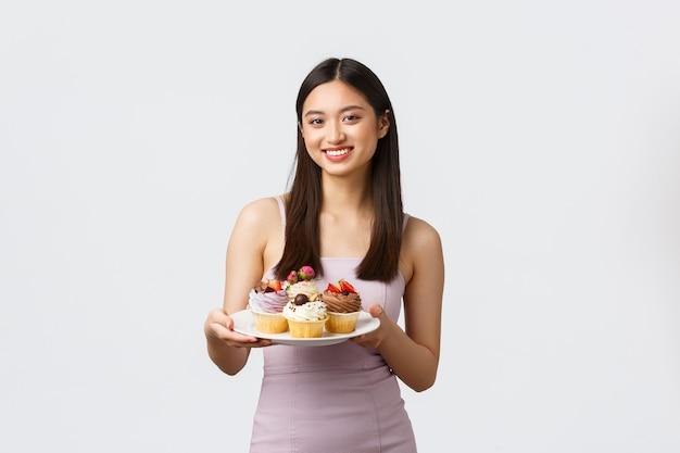 라이프 스타일, 휴일, 축하 및 음식 개념. 이브닝 드레스에 아름 다운 젊은 아시아 여자, 맛있는 디저트로 손님 대우